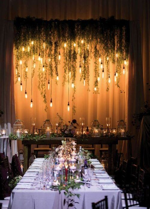 candle lanterns, floating candles and hanging bulbs create a magical and beautiful look in the space