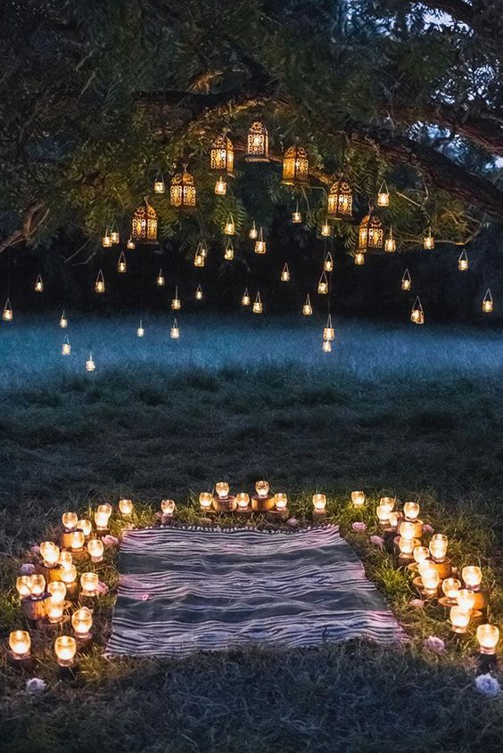 candleholders surrounding the space, candle lanterns and Moroccan lanterns hanging over it make it wow
