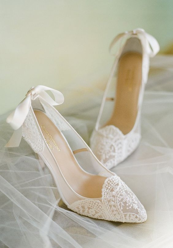 delicate sheer white lace wedding shoes with ribbon bows and pointed toes are a soft romantic touch