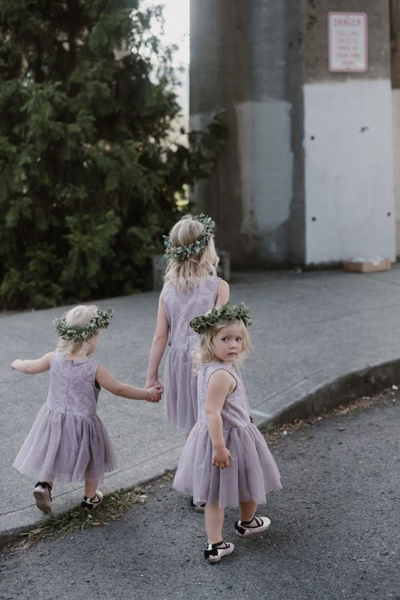 lavender midi flower girl dresses with lace bodices and pleated skirts, greenery crowns and flat shoes