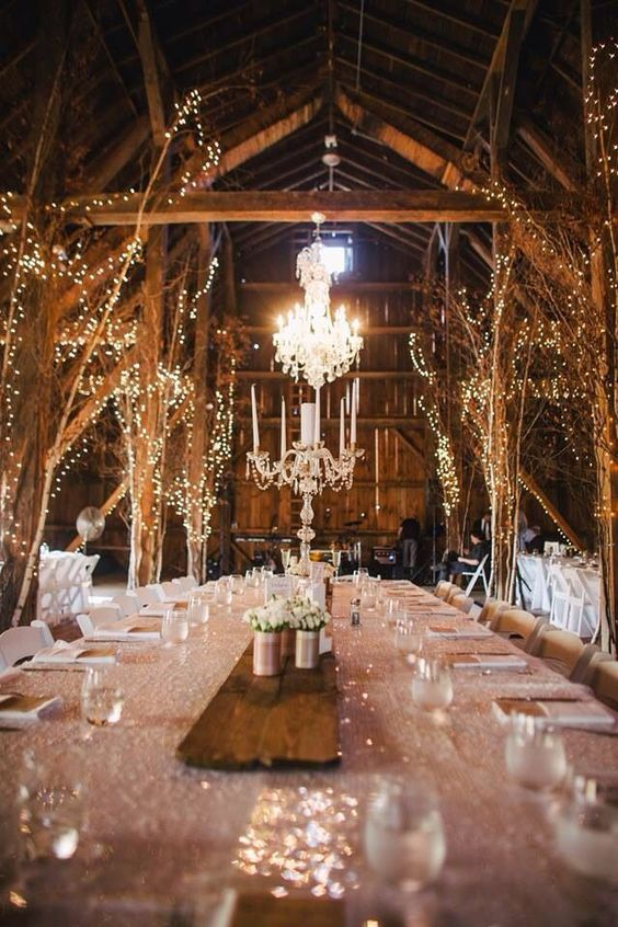 lit up trees and crystal chandeliers create a whimsical winter wonderland feel in the space