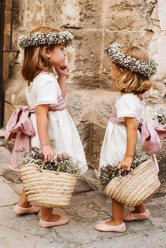 white over the knee flower girl dresses with pink sashes and bows, floral crowns and woven bags with blooms