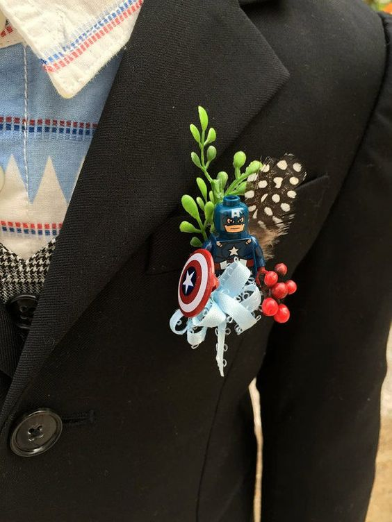 a Captain America wedding boutonniere with a feather, greenery and berries is a creative idea for a big fan