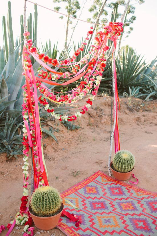 a Mexican fiesta wedding arch covered with bright blooms and ribbons and oversized potted cacti is bold and cool