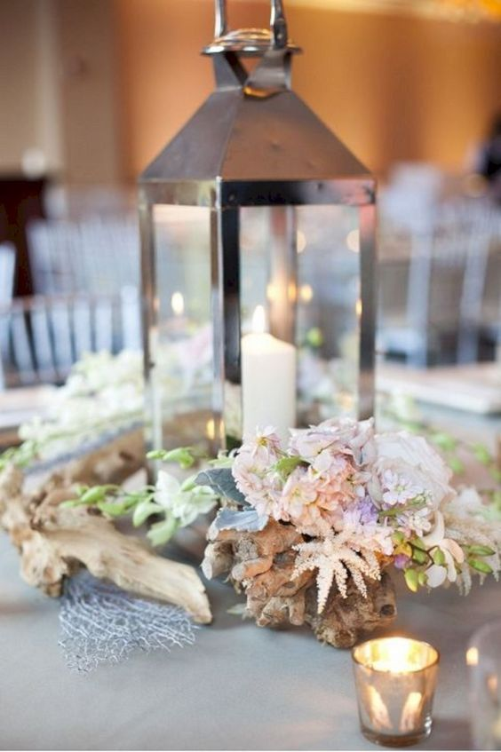 a beach wedding centerpiece with a metal candle lantern, driftwood, peastel blooms and greenery