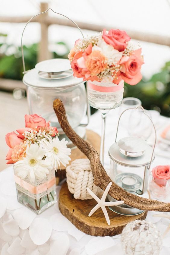 a beach wedding centerpiece with a wood slice, driftwood, candle lanterns and coral blooms plus rope