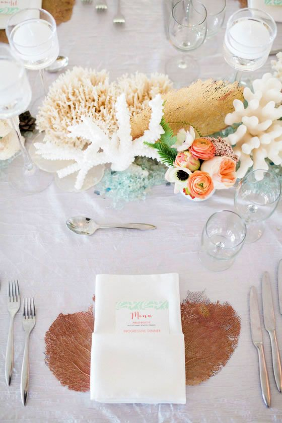 a beach wedding centerpiece with corals, sea sponges, sea glass, driftwood and peachy blooms