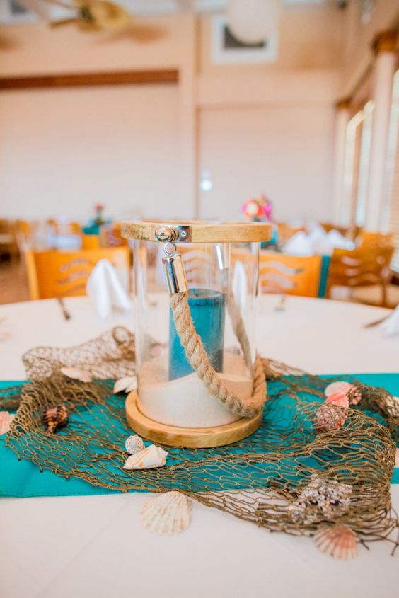 a beach wedding centerpiece with fishing net, seashells, a glass lantern with sand and a turquoise candle