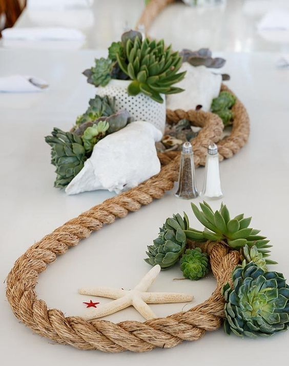 a beachy centerpiece with rope, succulents, starfish, a seashell and potted greenery