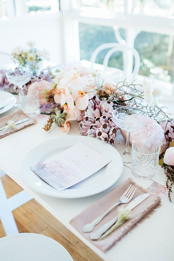 a beautiful beach wedding centerpiece with succulents, corals, peachy orhicds, branches and pink quartz