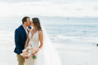 a beautiful embellished lace mermaid wedding dress with a deep plunging neckline, wide straps, a train for a glam beach bride