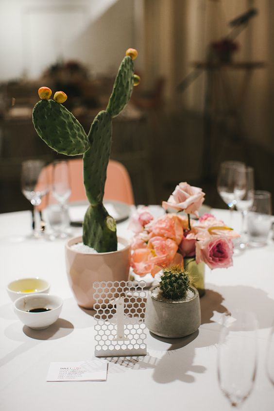 a beautiful wedding centerpiece of potted succulents, blush and peachy blooms and a laser cut table number