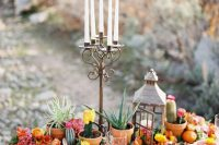 a bold wedding centerpiece of pink, orange and yellow blooms, potted cacti and succulents plus candles