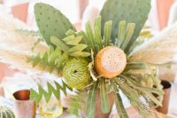 a bold wedding centerpiece of statement blooms, greenery and foliage and large cacti for a desert celebration