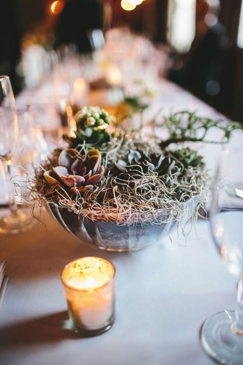 a bowl with planted succulents and hay is a simple and chic rustic wedding centerpiece idea