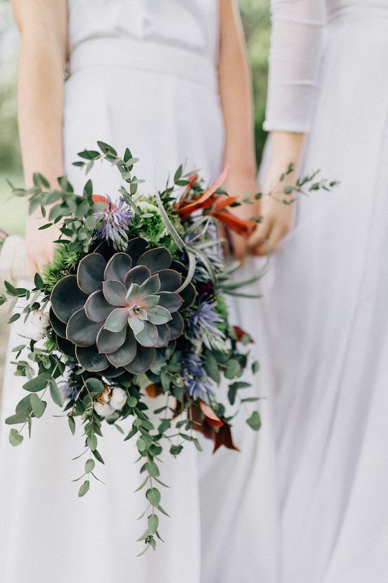 a cascading wedding bouquet of a large succulents, cascading greenery and small blooms is bold