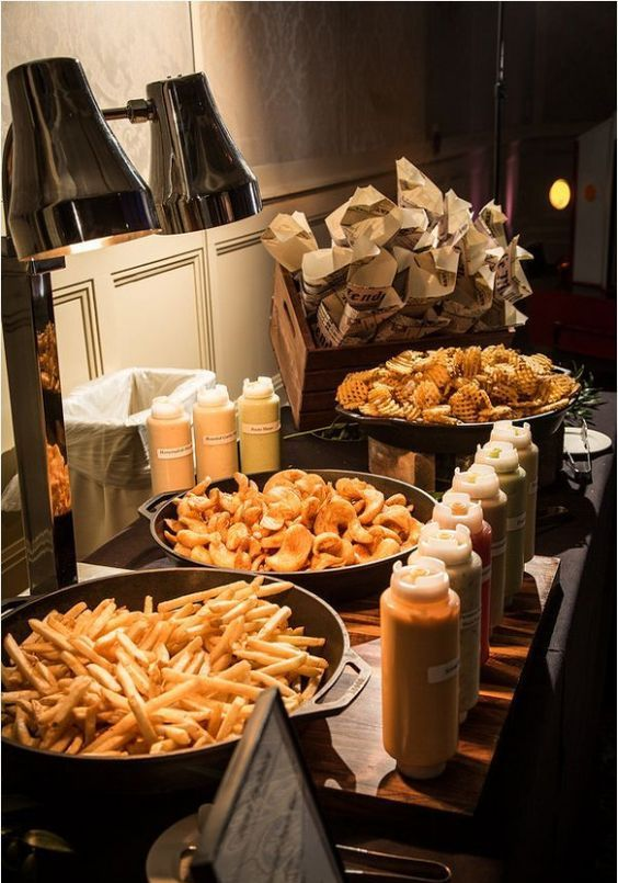 a casual wedding food bar with French fries, nachos and waffles, various dips, sauces and ketchups