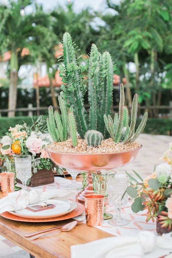 a catchy centerpiece of a copper bowl with lots of cacti growing in it is amazing and bold
