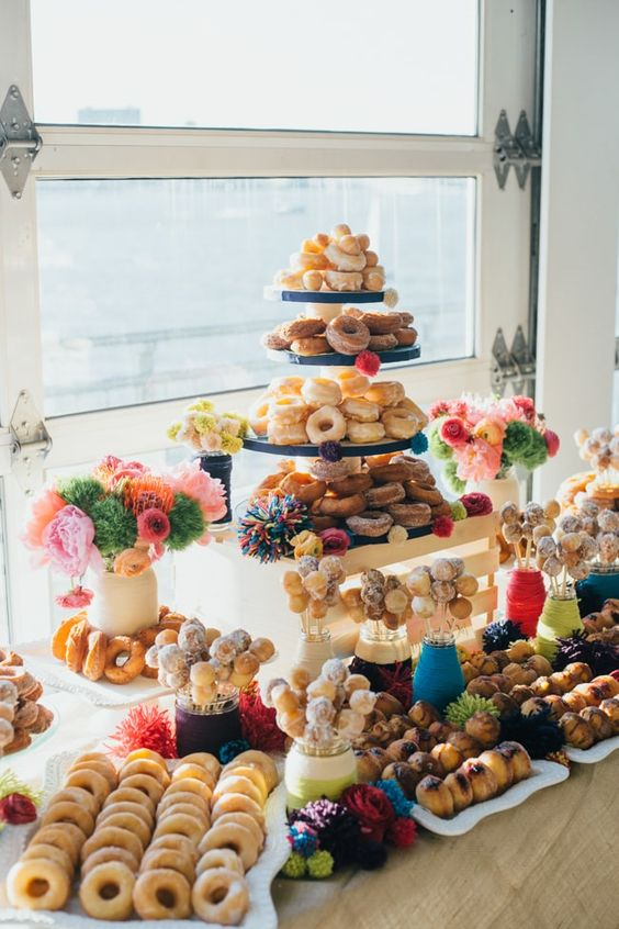 a colorful donut bar with bold pompom decor and bright blooms is amazing for a bright wedding