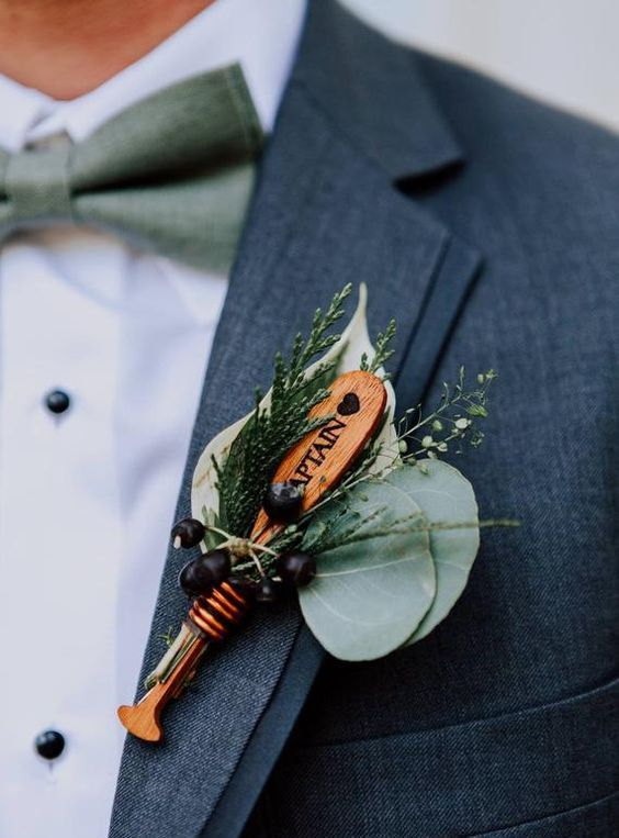a cool wedding boutonniere of berries, greenery, an oar is a lovely idea for those who like such sport or for a lake