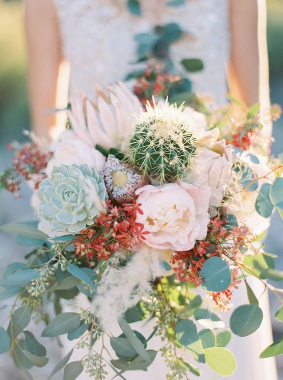 a creative and wild wedding bouquet with lush blooms, red ones, greenery, succulents and cacti is lovely