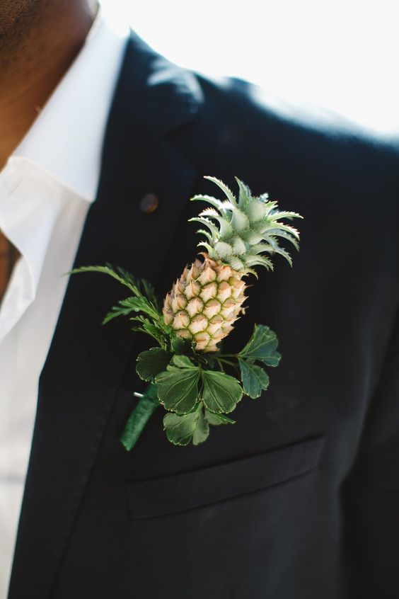 a creative wedding boutonniere of a mini pineapple with greenery is a perfect idea for a tropical wedding or for a glam summer one