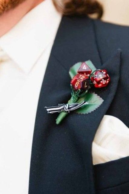 a creative wedding boutonniere of silk leaves, red dices and a striped bow is a fun idea for a groom who loves to play