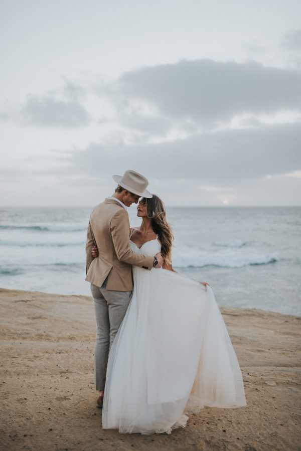 a cute and romantic A-line wedding dress with a lace bodice, a flowy skirt, spaghetti straps for a beach bride