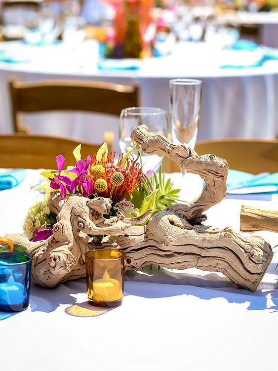 a driftwood wedding centerpiece with bright tropical blooms and candles in colorful glass candle holders
