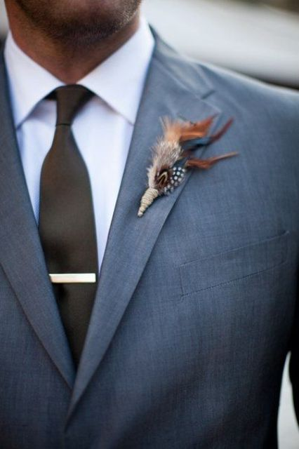 a feather wedding boutonniere wiht a twine wrap will give a slight boho touch to your groom's look