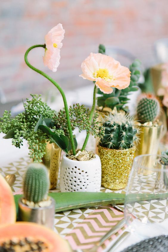 a glam wedding centerpiece of potted blooms, cacti and greenery in white and glitter planters