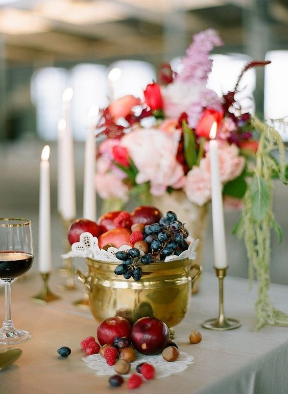 a golden pot with various fruit - grapes, pomegranates, apples and plums is a cute and lush centerpiece idea