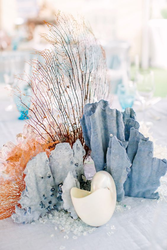 a gorgeous beach wedding centerpiece in light blue and coral plus shells and corals looks really unique