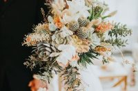 a gorgeous desert wedding bouquet of succulents, cacti, white and orange blooms and greenery