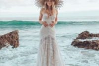 a lace strapless sheath wedding gown plus a fringe straw hat for a fahsionable isle bride