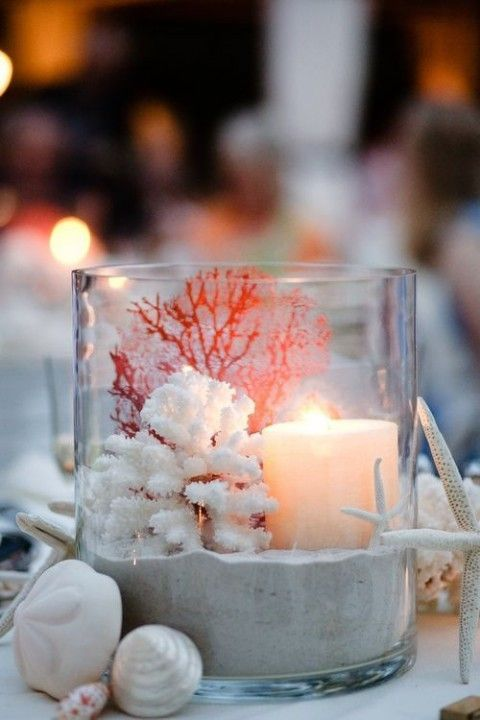 a large glass with sand, corals, a star fish, a candle and seashells plus starfish all around for a beach wedding