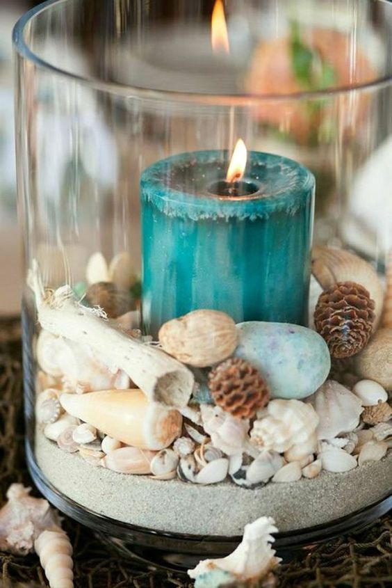 a large glass with sand, seashells, nuts, pebbles and a teal candle plus seashells and starfish all around