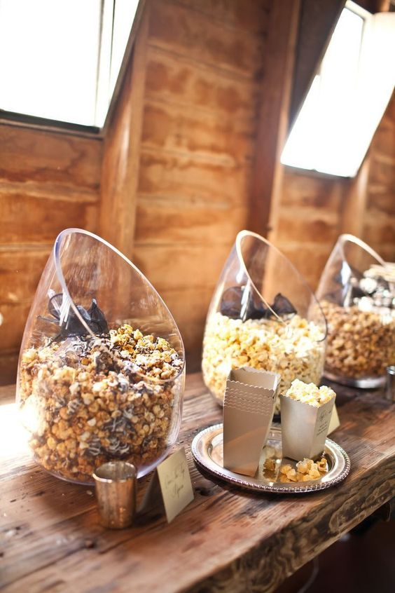 a modern wedding popcorn bar with angled glass jars and some cardboard bags for storing