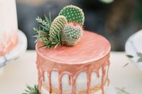 a naked wedding cake with copper drop, greenery and some cacti on top looks lovely