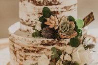 a naked wedding cake with greenery, succulents, thistles and white blooms for a rustic wedding