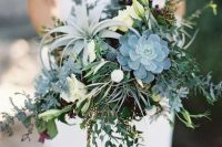 a neutral wedding centerpiece of greenery, succulents, airplants, thistles and white blooms is romantic
