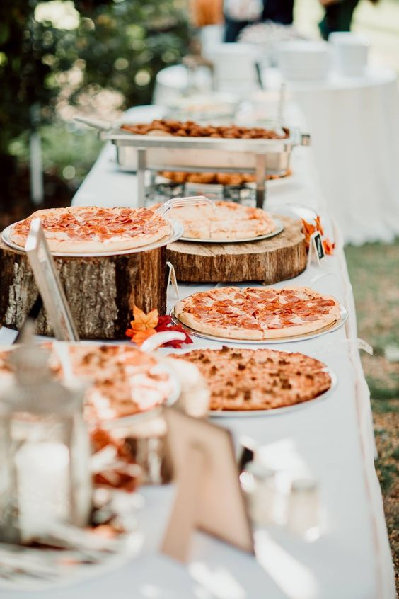 a pizza bar with pizzas on tree stumps and slices or on plates plus condiments and other food