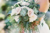 a romantic wedding bouquet with blush roses, greenery, berries, succulents and cacti is a gorgeous statement
