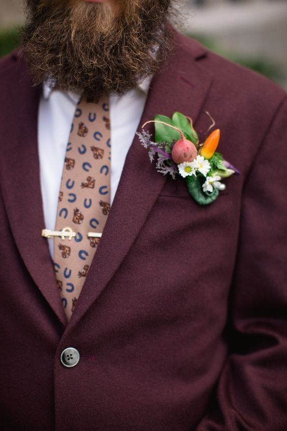 a rustic foodie summer wedding boutonniere of leaves, white blooms, radish and a pepper is a fun idea for a fall wedding, too