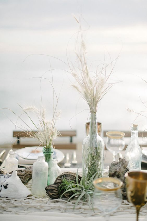 a seaside wedding centerpiece with driftwood, air plants, dried herbs, sea glass and fishing net