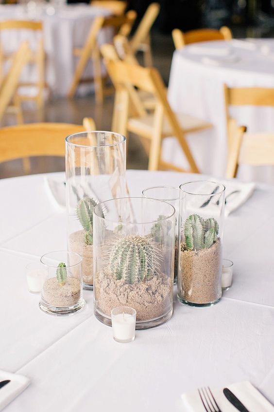 a simple desert wedding centerpiece of cacti planted in tall glasses and candles is a stylish idea