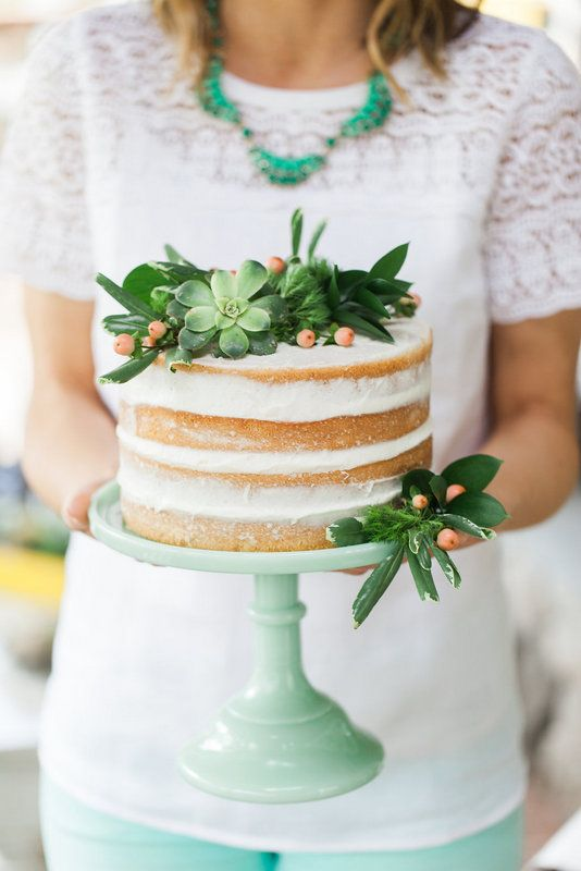 a simple naked cake topped with succulents, berries and greenery for a modern rustic wedding