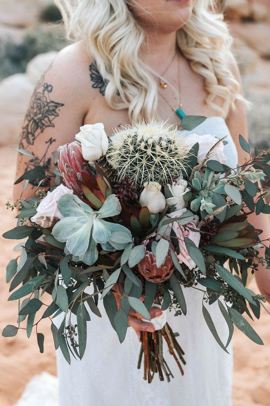 a stylish wedding bouquet of greenery, white and blush roses, succulents and a large cactus in the center