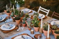 a stylish wedding tablescape with a potted succulent and greenery table runner and candles plus touches of wood