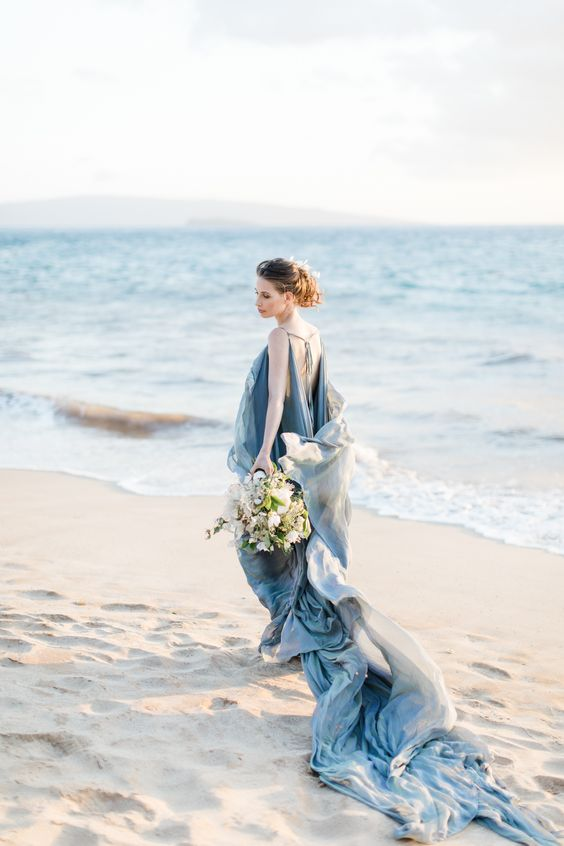a super flowy and airy blue wedding dress with layers of fabric, a cutout back with ties and a train for a sea-loving bride